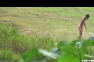 brunette teen caught outdoors oiling milk sacks